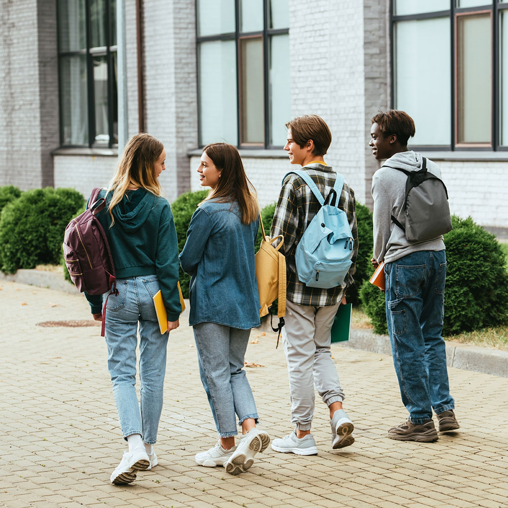 42823841 Back View Of Smiling Teenagers With Backpacks Walking On